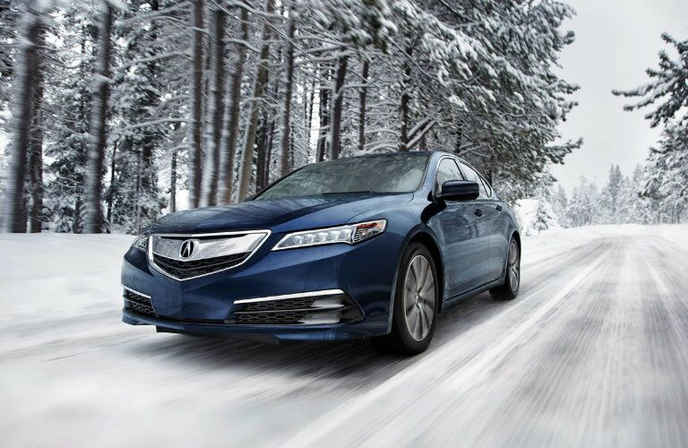 blue 2017 Acura TLX driving through snow