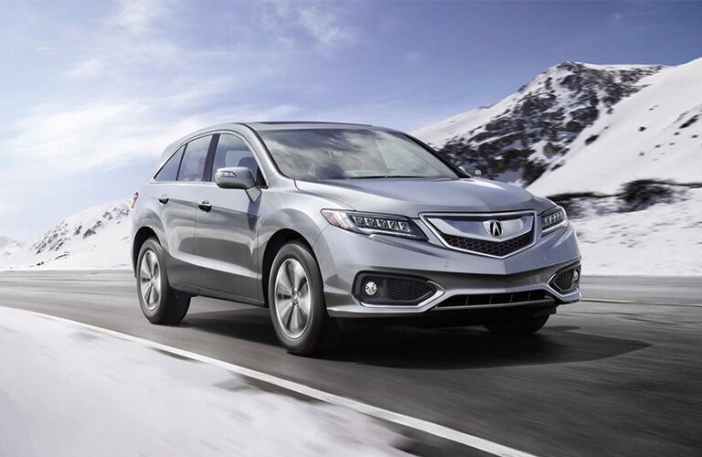 2018 Acura RDX driving past snowy mountains
