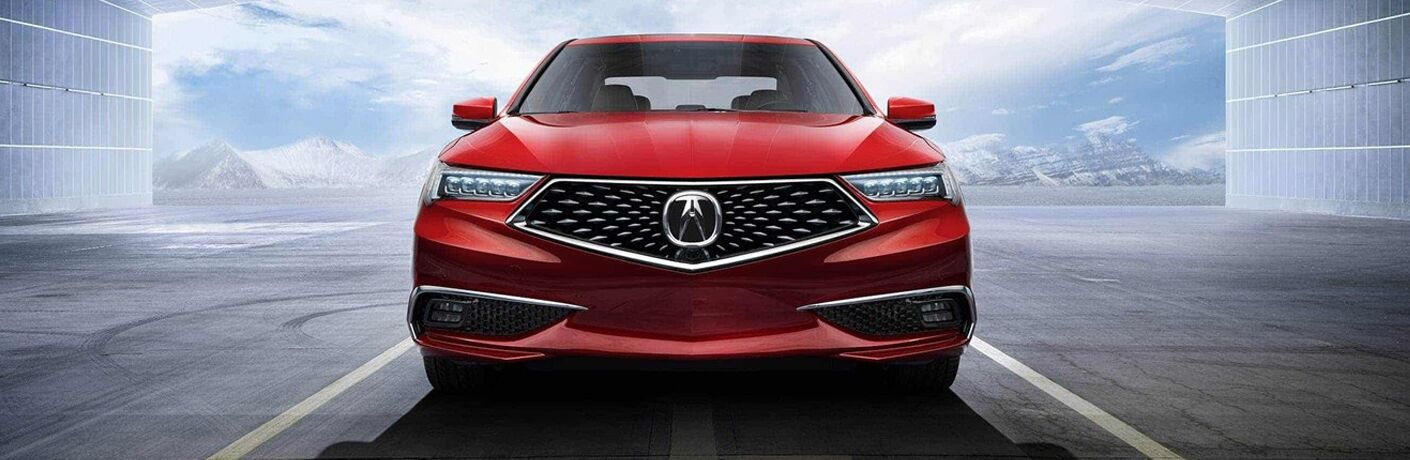 Red 2019 Acura TLX with mountains in the background and large warehouse surroundings