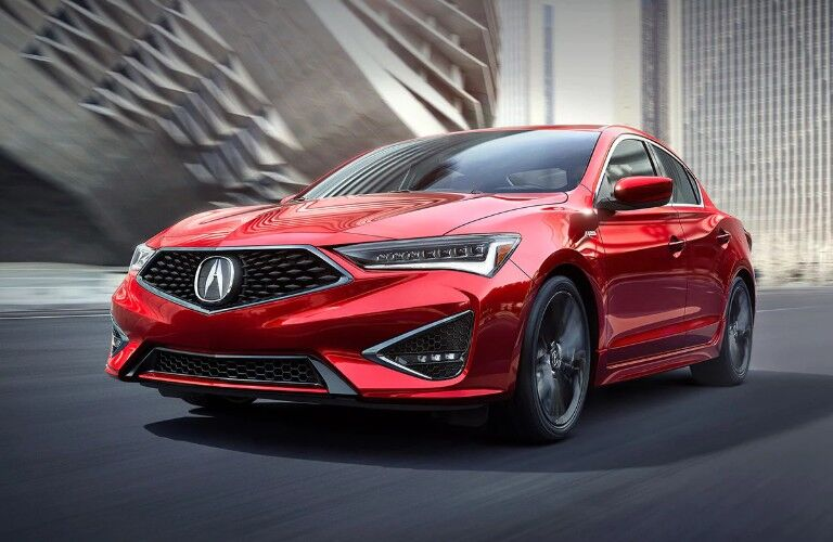 Front driver angle of a red 2019 Acura ILX driving down a road