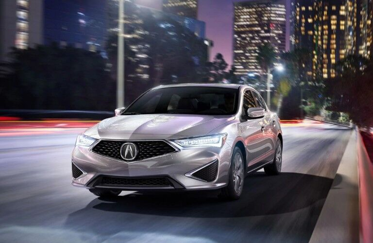 Front driver angle of a silver 2020 Acura ILX driving down a city street
