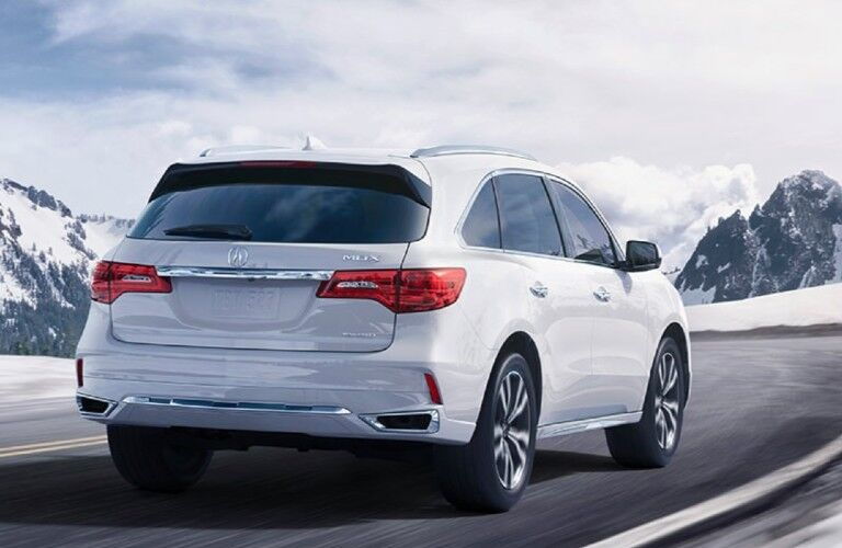 Rear passenger angle of a white 2020 Acura MDX driving on a road