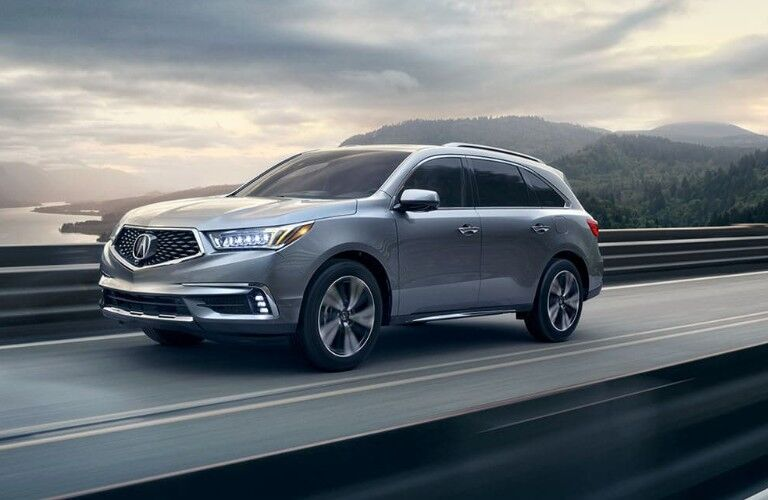 Front driver angle of a silver 2020 Acura MDX driving down a road
