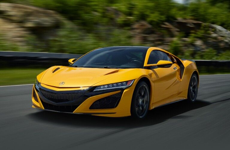 Front driver angle of a yellow 2020 Acura NSX driving down a road