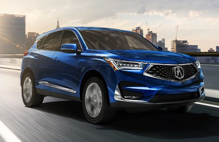 Front passenger angle of a blue 2020 Acura RDX driving down a road