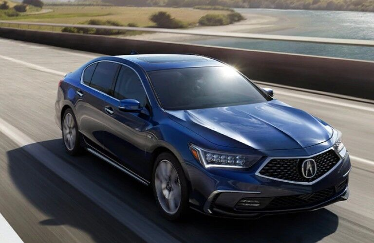 Front passenger angle of a blue 2020 Acura RLX driving on a road