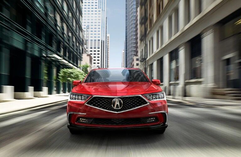 Front view of a red 2020 Acura RLX driving down a city street