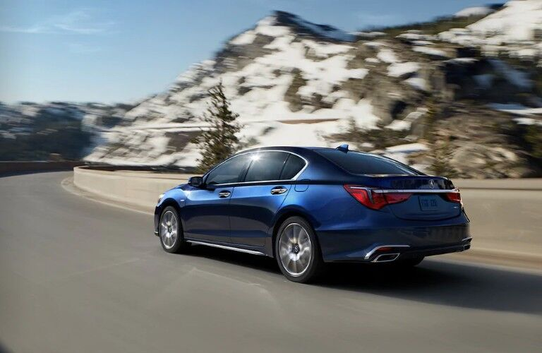 Rear driver angle of a blue 2020 Acura RLX driving on a road with a snowy mountain in the background