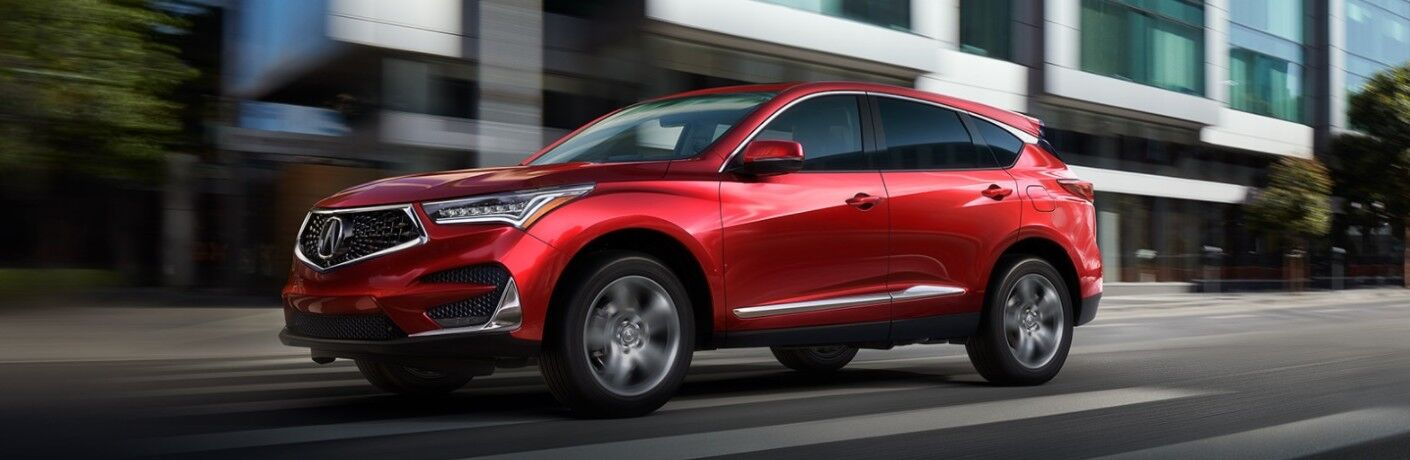 Front driver angle of a red 2021 Acura MDX driving in a city