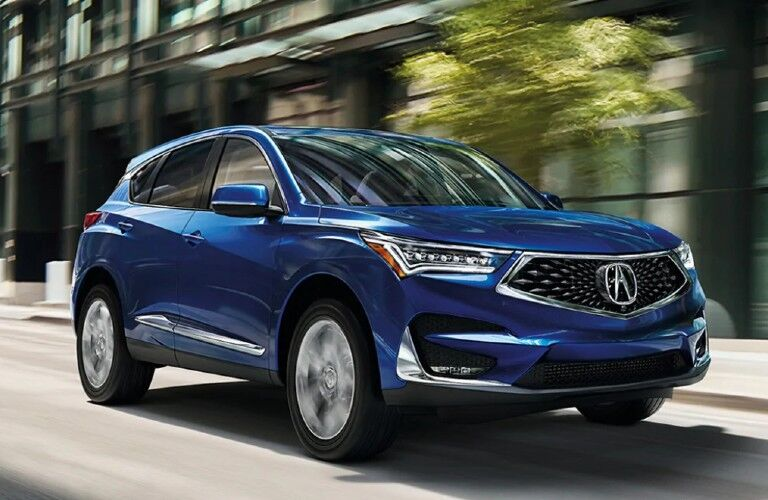 Front passenger angle of a blue 2021 Acura RDX driving in a city