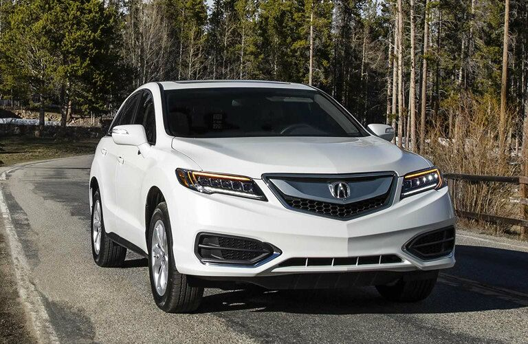 White 2017 Acura RDX driving along forest road