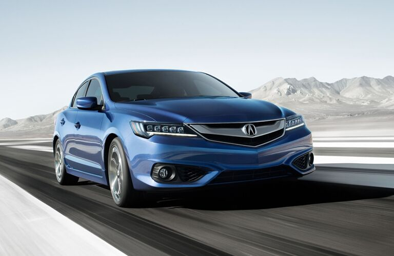 Front passenger angle of a blue Acura ILX driving down a road