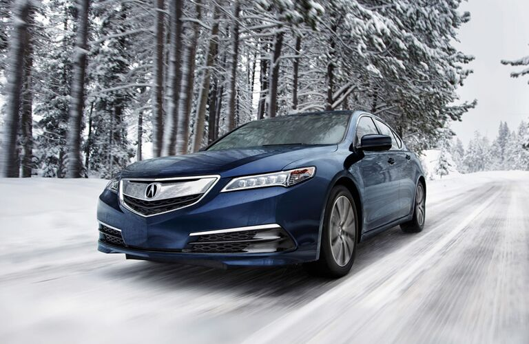 Front driver angle of a blue Acura TLX driving down a snowy road