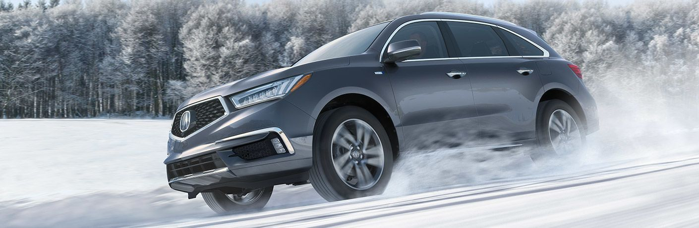 Platinum gray 2019 Acura MDX driving through snow