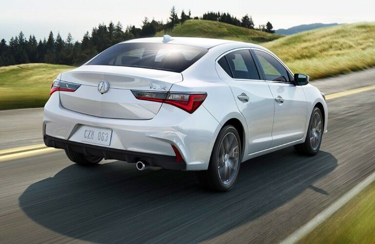 Rear passenger angle of a white 2020 Acura ILX driving down a road