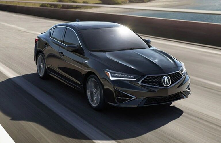 Front passenger angle of a black 2020 Acura ILX driving down a road
