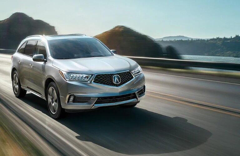 Front passenger angle of a silver 2020 Acura MDX driving down a road