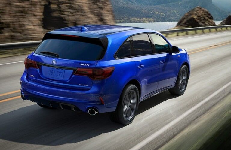 Rear passenger angle of a blue 2020 Acura MDX A-Spec Package driving down a road