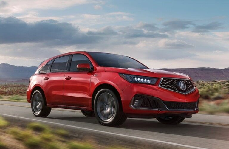 Front passenger angle of a red 2020 Acura MDX A-Spec Package driving down a road