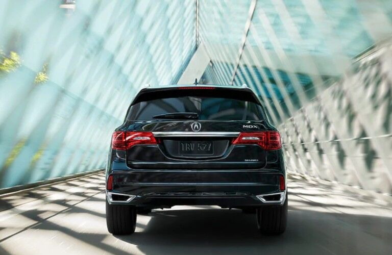Rear angle of a black 2020 Acura MDX Advance Package driving down a road