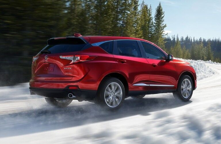 Rear passenger angle of a red 2020 Acura RDX driving in snow