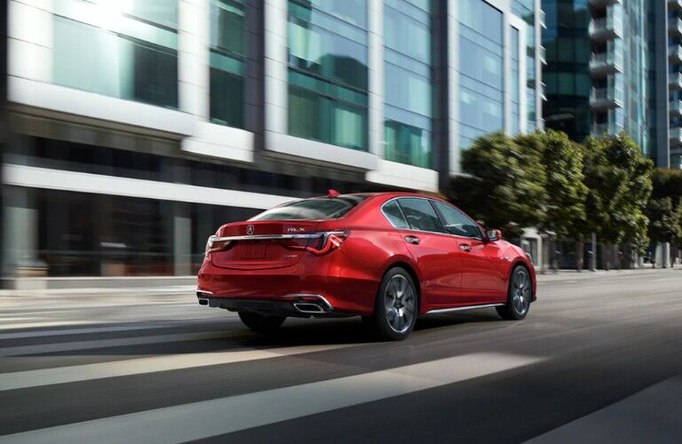 Rear passenger angle of a red 2020 Acura RLX driving through a city