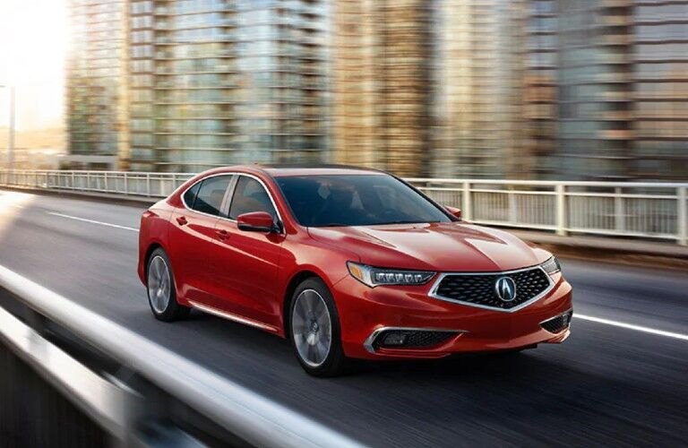 Front passenger angle of a red 2020 Acura TLX driving in a city