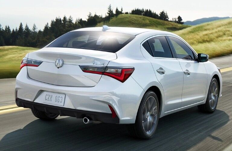 Rear passenger angle of a white 2021 Acura ILX Premium Package driving on a road