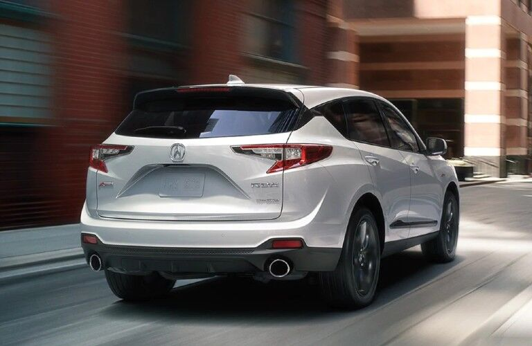 Rear passenger angle of a white 2021 Acura RDX A-Spec Package driving on a road