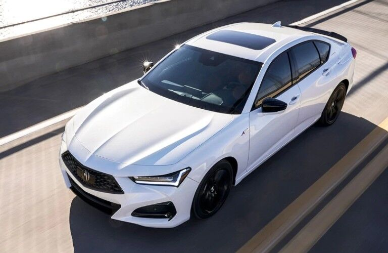 Front driver angle of a white 2021 Acura TLX A-Spec Package driving on a road
