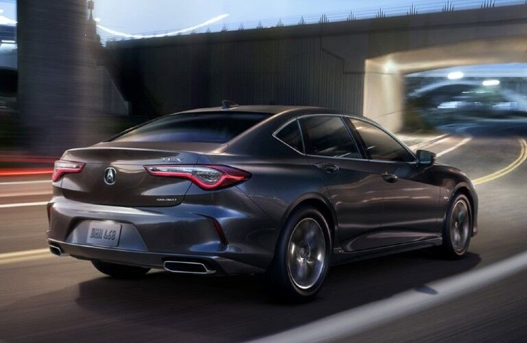 Rear passenger angle of a dark grey 2021 Acura TLX driving on a road