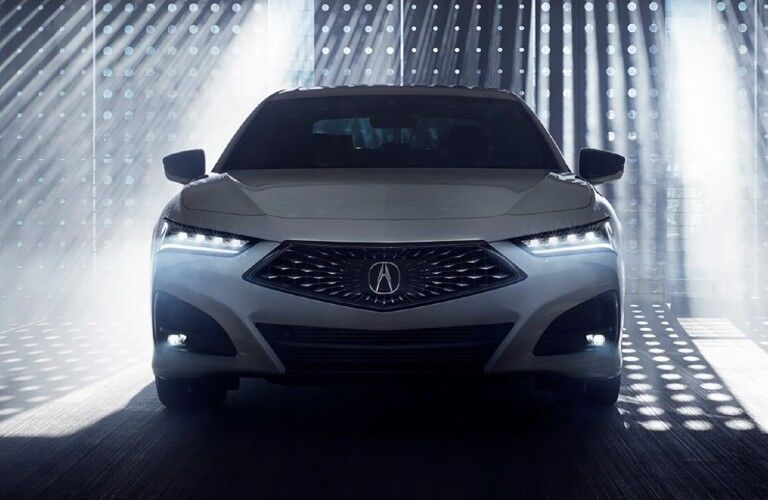Front angle of a white 2021 Acura TLX with lights behind it