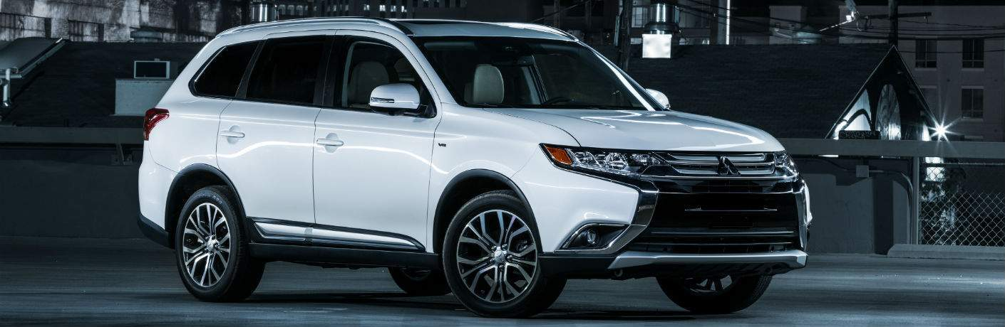 A front right quarter photo of the 2018 Mitsubishi Outlander parked in front of buildings at night.