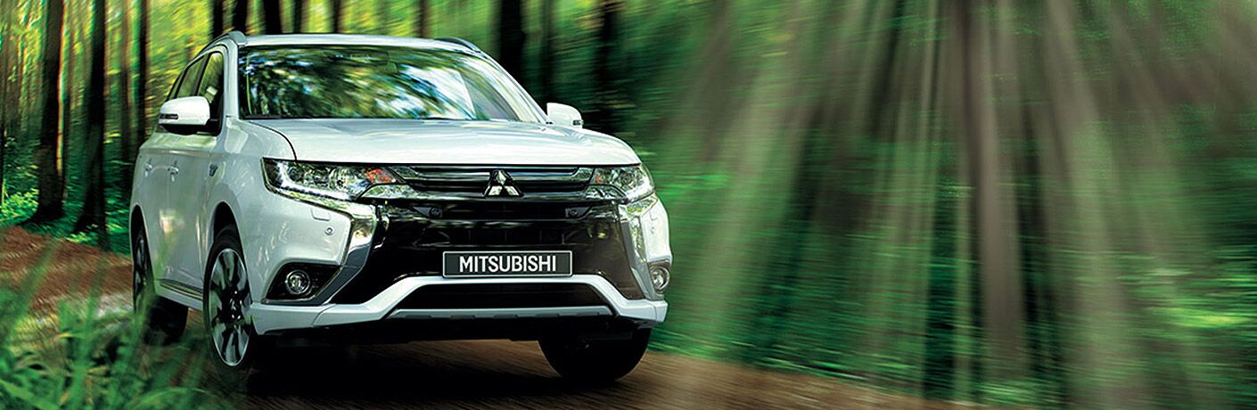 A head-on photo of the 2018 Mitsubishi Outlander PHEV driving through the woods.