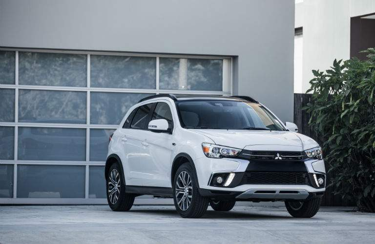 A front view of the 2018 Mitsubishi Outlander Sport in front of a garage door