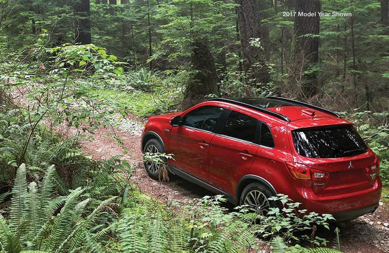 A red 2018 Mitsubishi Outlander Sport driving from right to left on a trail in the woods