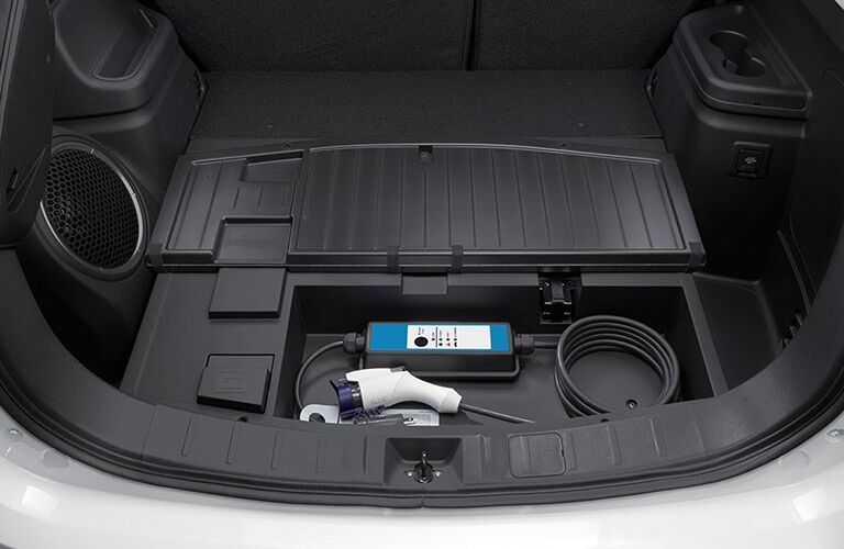 A photo of the cargo area in the 2018 Mitsubishi Outlander PHEV where the charging gear is stored.