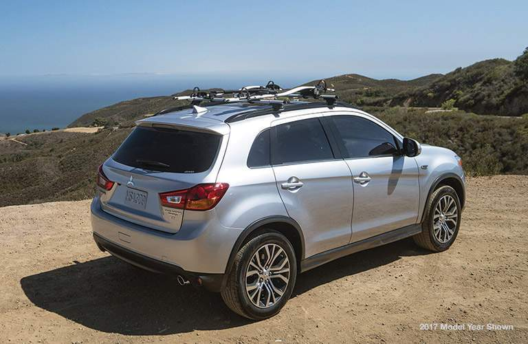 A silver 2018 Mitsubishi Outlander Sport overlooking mountains and the ocean with a rear quarter view of the vehicle