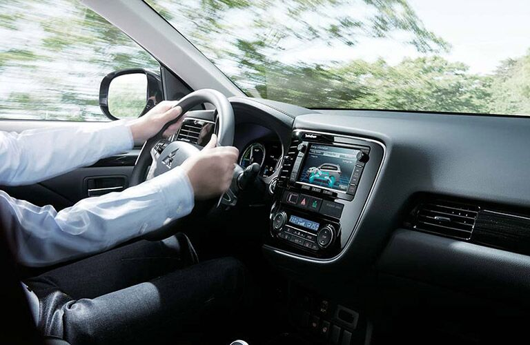 An interior photo showing a driver behind the wheel of the 2018 Mitsubishi Outlander PHEV.