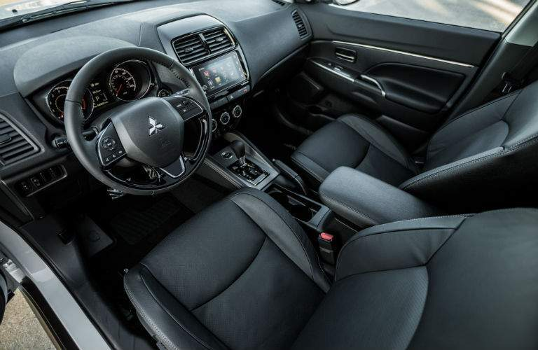 An interior view of the driver's cockpit of the 2018 Outlander Sport including the infotainment system and center gauge cluster