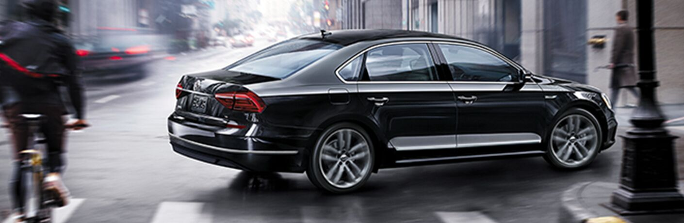 Exterior view of a black 2019 Volkswagen Passat turning down a city street
