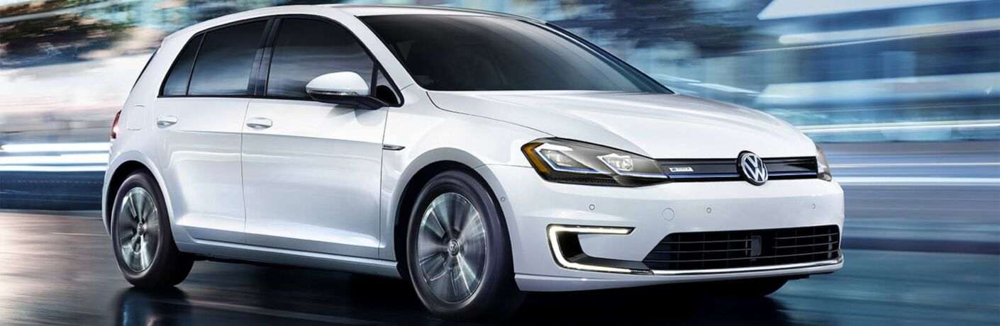 Exterior view of a white 2018 Volkswagen e-Golf driving down a city street