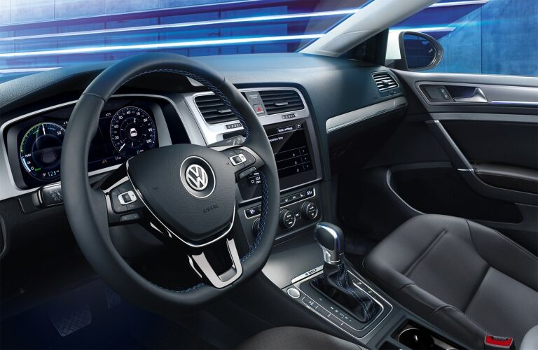 Interior view of the black steering wheel and touchscreen inside a 2018 Volkswagen e-Golf