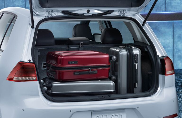 Exterior view of the rear of white 2018 Volkswagen e-Golf with the hatch open showing the cargo area full of luggage