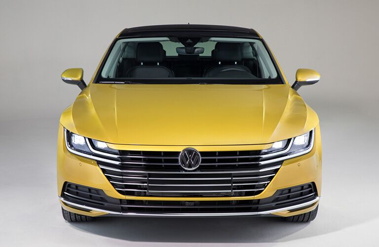 Exterior view of the front of a yellow 2019 Volkswagen Arteon parked in a white showroom