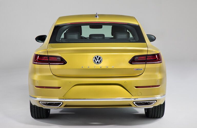 Exterior view of the rear of a yellow 2019 Volkswagen Arteon parked in a white showroom