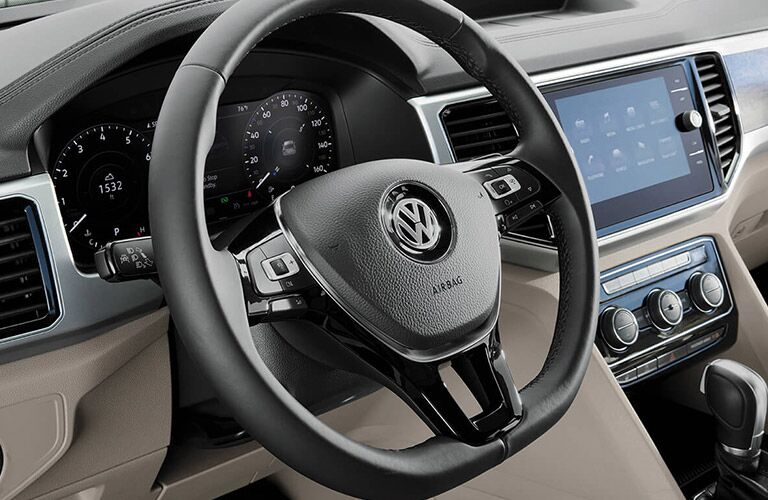 Closeup view of the black steering wheel and touchscreen inside a 2019 Volkswagen Atlas