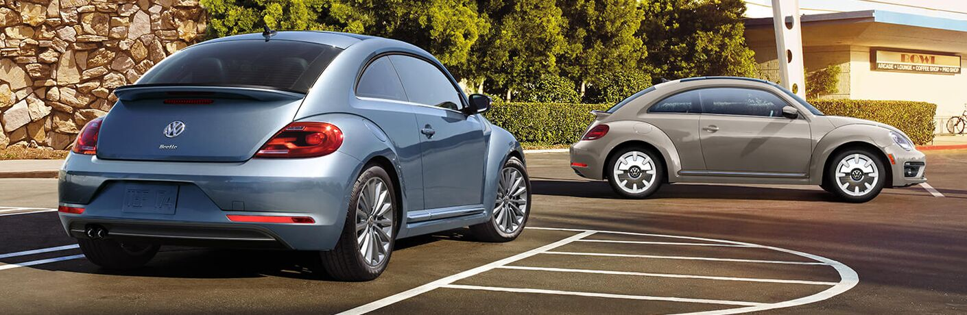 Exterior view of a light-blue VW Beetle and a tan VW Beetle parked in a city parking lot
