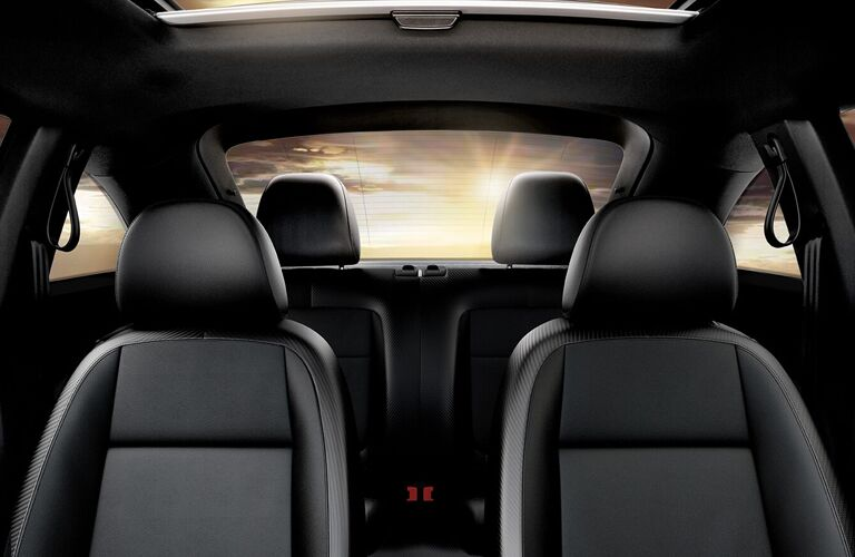 Interior view of the black seating inside a 2019 Volkswagen Beetle with a sunset shining through the rear window