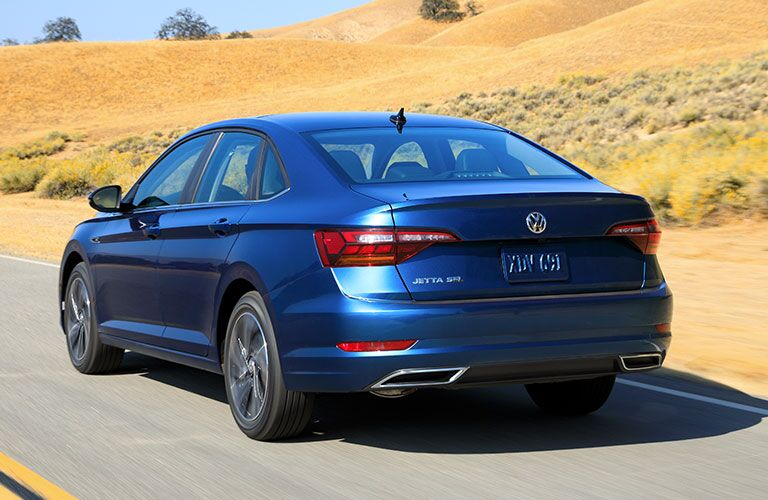 Exterior view of the rear of a blue 2019 Volkswagen Jetta driving down a highway during the day